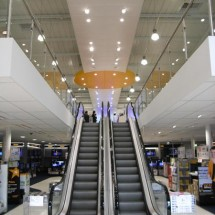 Retail mezzanine with escalator showing a large cantilever and stainless-glass balustrade