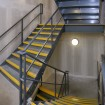 Internal fire escape stairs with chequer plate treads and contrasting yellow painted nosing complete with stringer mounted round tube